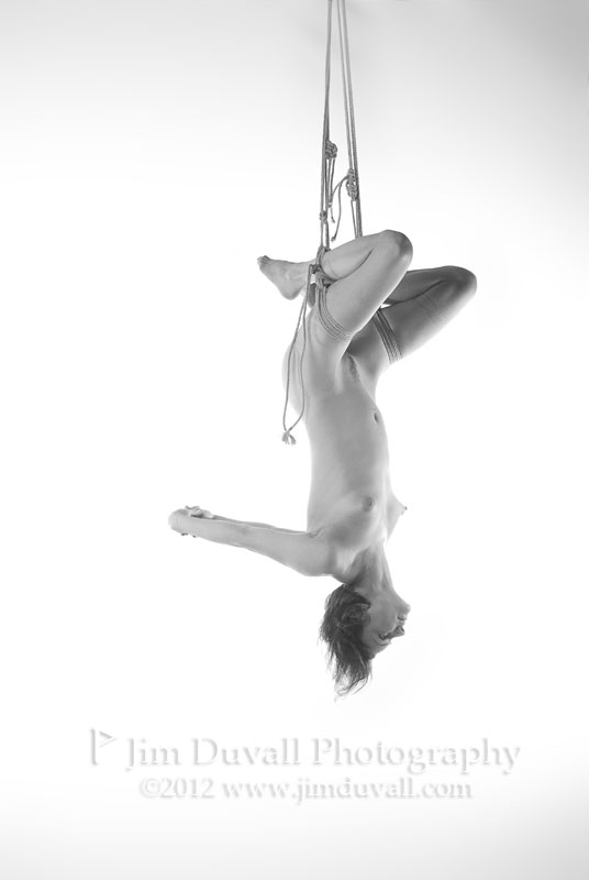 nude woman tied upside down by both legs