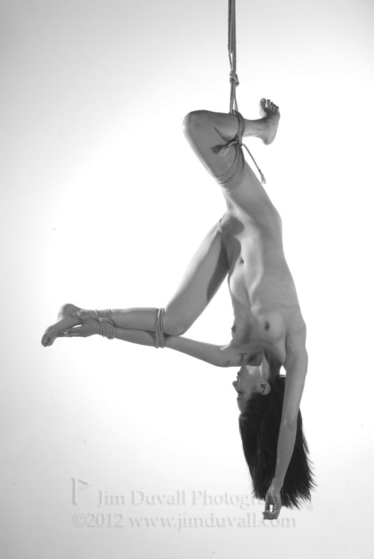 A woman hung upside down by one leg Model: Mitsu