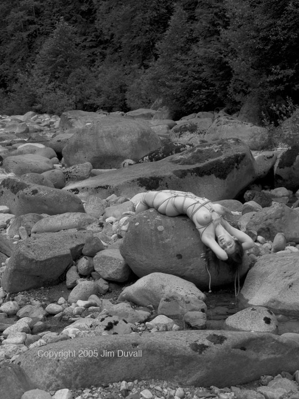 woman bound and layng on rocks near a river