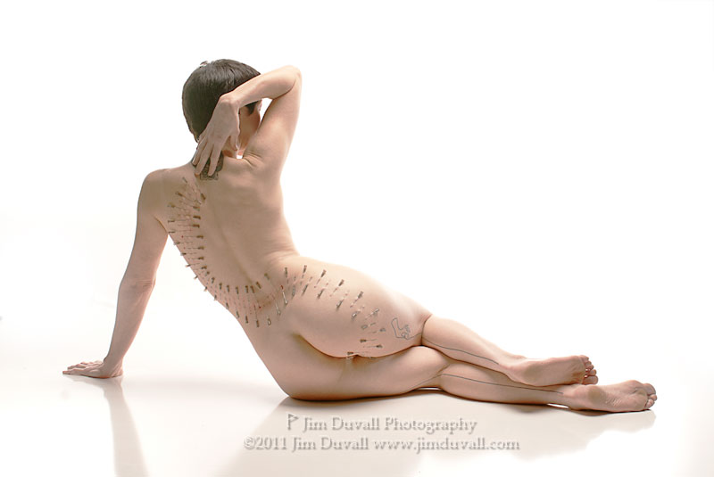 Woman with needles in her back in an artistic pattern
