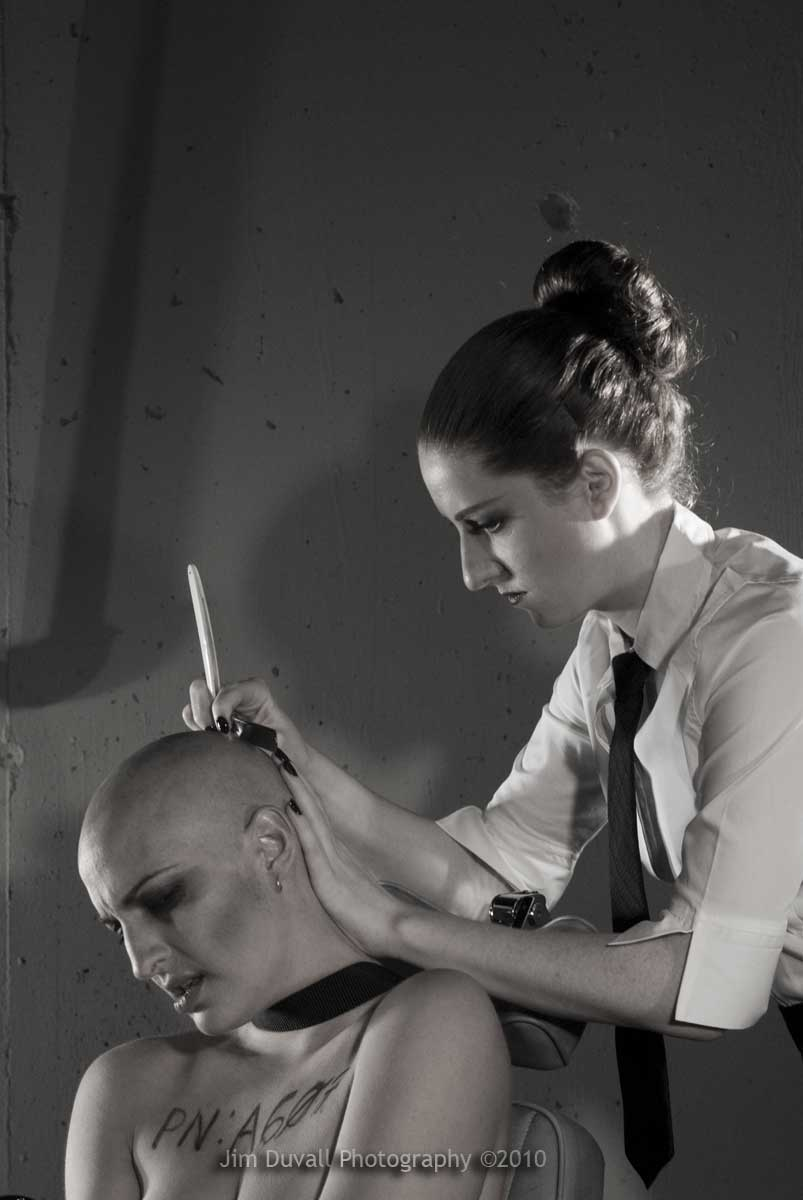Nude woman bound, with another women shaving her ehad with a straight razor
