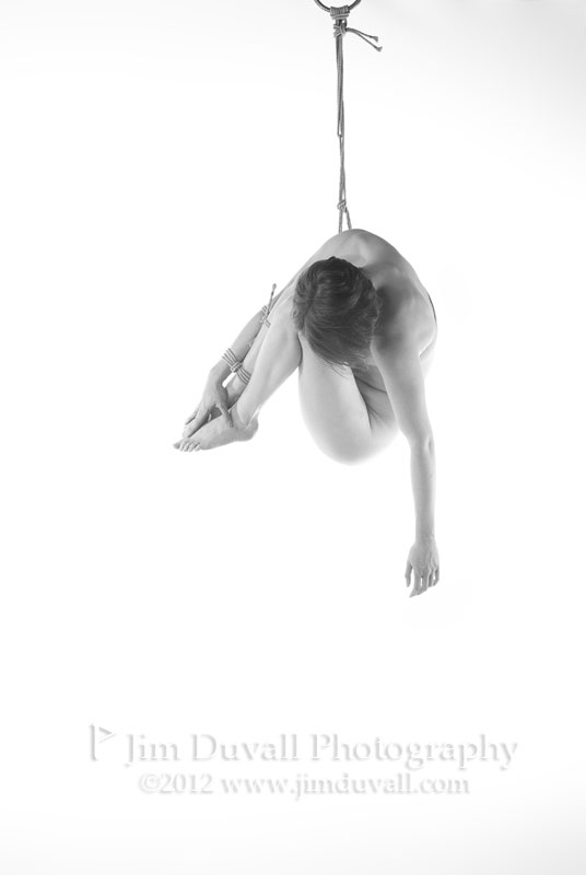 nude woman hanging in a ball