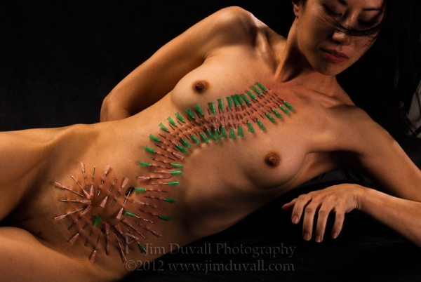 Woman with needles in he body in an artistic pattern