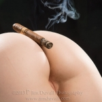 Womans ass with a lit cigar resting on it